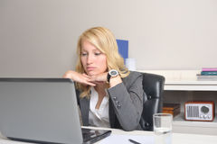 Businesswoman disapointed at work. Young blonde businesswoman disapointed behind her laptop at the office Royalty Free Stock Image