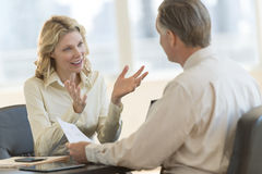 Businesswoman Discussing With Colleague In Office. Mature businesswoman discussing with male colleague in office Royalty Free Stock Photography