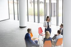 Businesswoman discussing with colleagues during meeting at office royalty free stock photography