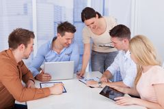 Businesswoman discussing with colleagues in office. Young businesswoman discussing with colleagues during conference meeting royalty free stock photography