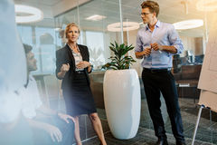 Businesswoman discussing with colleagues during presentation Stock Image