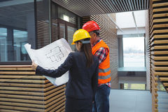 Businesswoman discussing over blueprint with a architect Stock Photos