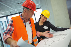 Businesswoman discussing over blueprint with a architect Royalty Free Stock Image