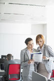 Businesswoman discussing over book in office Royalty Free Stock Photos