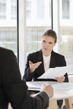 Businesswoman discussing over documents with colleague in office cafe Royalty Free Stock Photos