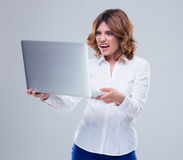 Businesswoman with disgusted emotion holding laptop. Over gray background stock photos