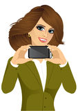 Businesswoman displaying her smartphone. Portrait of beautiful brunette businesswoman displaying her smartphone on horizontal position  on white background Royalty Free Stock Photography