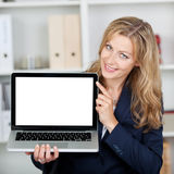 Businesswoman Displaying Laptop With Blank Screen In Office. Mid adult businesswoman displaying laptop with blank screen in office stock photography