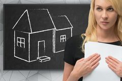 Businesswoman. With documents and drawing house on blackboard Stock Photography