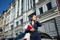 Businesswoman. With documents and tablet in hand, talking on the phone on the background of vintage buildings Stock Photo