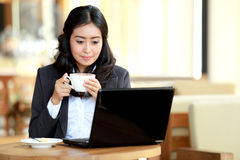 Businesswoman doing her work while taking a coffee break Royalty Free Stock Photos