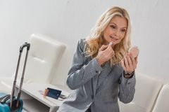 Businesswoman doing makeup before trip. Happy mature businesswoman doing makeup before trip Stock Photo