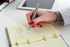 Businesswoman  doing mathematical calculations Stock Photo