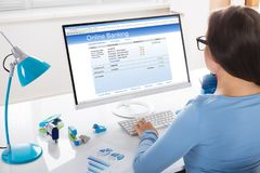 Businesswoman Doing Online Banking. Close-up Of A Businesswoman Doing Online Banking In Office stock photo