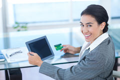 Businesswoman doing online shopping in office Stock Photography
