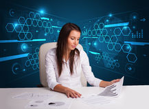 Businesswoman doing paperwork with futuristic background. Young businesswoman doing paperwork with futuristic background Stock Photo