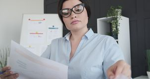Businesswoman doing paperwork at office. Businesswoman doing paperwork and making notes at office stock video