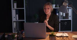Businesswoman doing video conference late night at office stock video footage