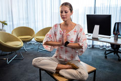 Businesswoman doing yoga with hands tied Stock Photo