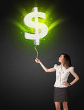 Businesswoman with a dollar sign balloon. Businesswoman holding a shining, green dollar sign balloon Royalty Free Stock Photo
