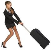 Businesswoman dragging heavy wheeled suitcase with Stock Photography
