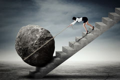 Businesswoman dragging stone on ladder Royalty Free Stock Image