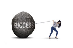 Businesswoman dragging success word on studio. Beautiful businesswoman dragging big stone with success word, isolated on white background Royalty Free Stock Image