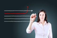Businesswoman drawing arrows in different directions. Blue background. Stock Images