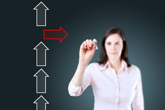Businesswoman drawing arrows in different directions. Blue background. Stock Photography