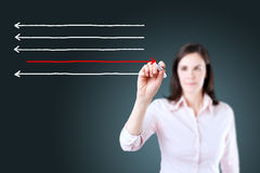 Businesswoman drawing arrows in different directions. Blue background. Royalty Free Stock Images