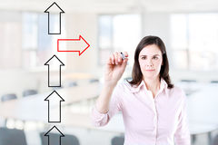 Businesswoman drawing arrows in different directions. Office background. Royalty Free Stock Photos