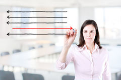Businesswoman drawing arrows in different directions. Office background. Royalty Free Stock Photography