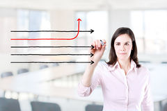 Businesswoman drawing arrows in different directions. Office background. Stock Image