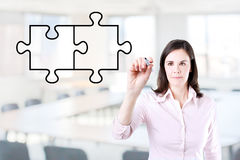 Businesswoman drawing a Blank Puzzle on the screen. Office background. Stock Photography