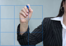 Businesswoman Drawing A Blue Graph Chart. Businesswoman drawing a blue chart with gray background Stock Images
