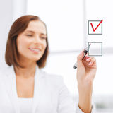 Businesswoman drawing chech into chechbox Stock Photos