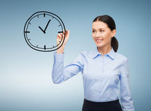 Businesswoman drawing clock in the air Royalty Free Stock Photography