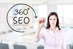 Businesswoman drawing a 360 degrees SEO concept on the virtual screen. Office background. Stock Photo