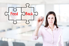 Businesswoman drawing a Feedback puzzle concept on the virtual screen. Office background. Stock Photos