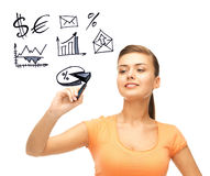 Businesswoman drawing financial signs. Business, finances and economics - businesswoman drawing financial signs in the air Royalty Free Stock Image