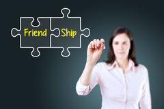 Businesswoman drawing a Friendship Puzzle Concept on the virtual screen. Blue background. Stock Photo