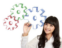 Businesswoman drawing gear cogs. Attractive beautiful businesswoman drawing gear cogs, isolated on white background Royalty Free Stock Images