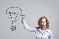 Businesswoman drawing and idea lamp on the Royalty Free Stock Images