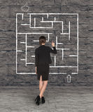 Businesswoman drawing labyrinth on wall Royalty Free Stock Images