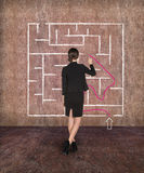 Businesswoman drawing labyrinth on wall Royalty Free Stock Photo