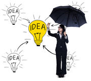 Businesswoman drawing light bulb Stock Photo