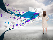 Businesswoman drawing on a paper next to paint splash Stock Photos