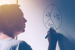Businesswoman drawing pie chart on office whiteboard. During business results analysis and presentation, selective focus Royalty Free Stock Photography