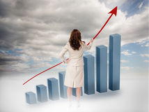 Businesswoman drawing a red arrow over a growing chart Royalty Free Stock Photo