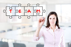 Businesswoman drawing a Teamwork Puzzle Concept on the virtual screen. Office background. Royalty Free Stock Images